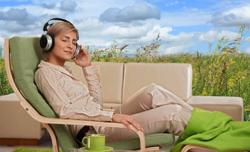 Woman with headphones, dreaming of being outdoors