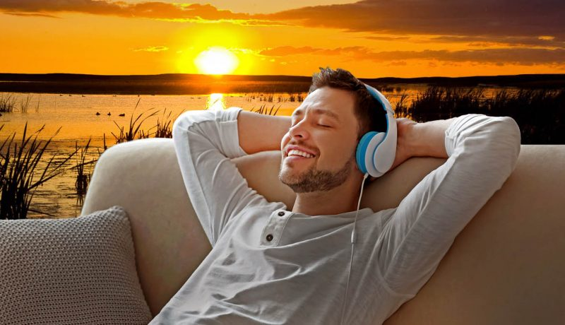 young man on couch with headphones, dreaming of the outdoors